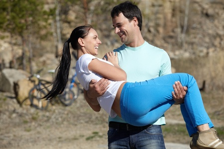 A young man carrying his girl in hands  photo
