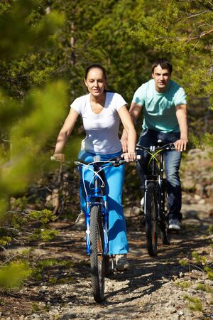 A young people riding bicycles in wood photo