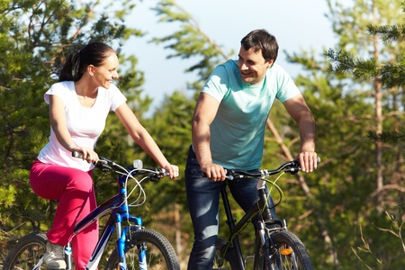 riding bike: A young happy couple riding bicycles together Stock Photo