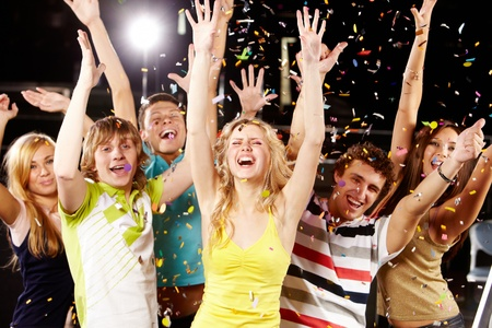 people partying: Photo of excited teenagers raising their arms in joy