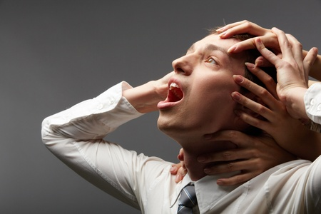 corporal: Portrait of a shouting businessman restrained by different hands