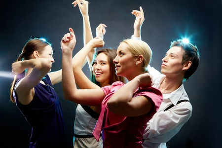 clubbing: Four dancing people isolated on black