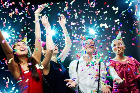 holiday celebration: Four friends making having fun among confetti  Stock Photo