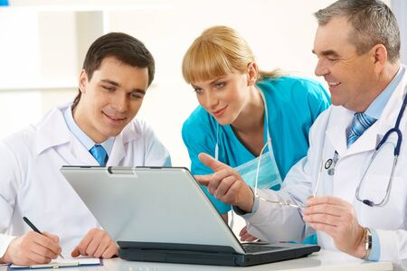 Photo of aged physician pointing at laptop display while explaining something to his colleagues photo