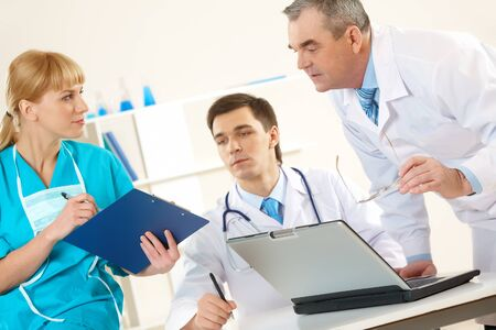 Photo of aged physician and young clinician looking at document in nurse's hand photo