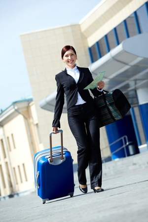 Image of businesswoman in suit walking with her baggage and bag photo