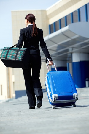 Rear view of businesswoman in suit walking with her baggage and bag photo