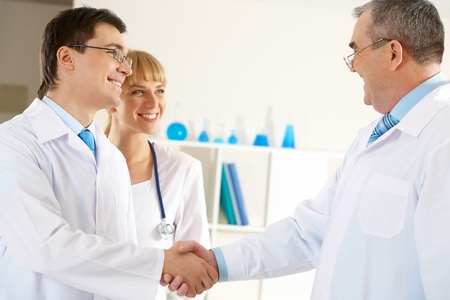 Photo of aged physician and young clinician handshaking with friendly nurse near by photo