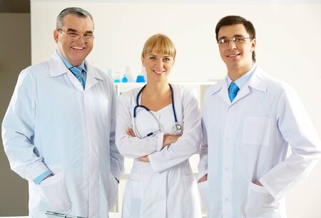 Portrait of friendly therapists standing in line and looking at camera with smiles photo
