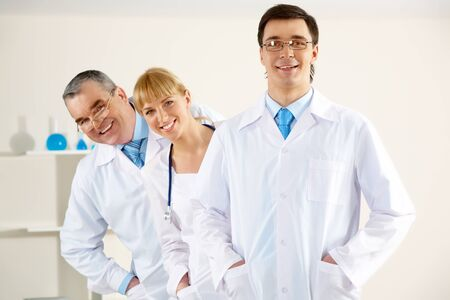 Portrait of friendly therapists standing in line and looking at camera with happy clinician in front photo