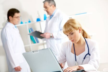 Photo of serious nurse with laptop planning work in working environment photo