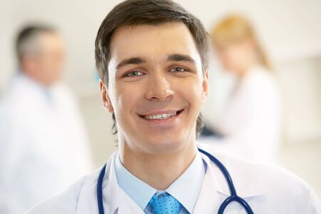 Portrait of cheerful doctor with stethoscope looking at camera and smiling photo
