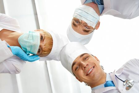 Below view of three therapeutists touching their heads while looking at camera photo