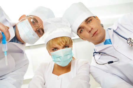 Three serious therapeutists touching their heads while looking at camera photo