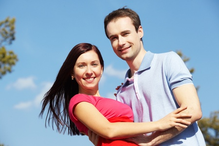 Portrait of happy couple looking at camera against blue sky photo