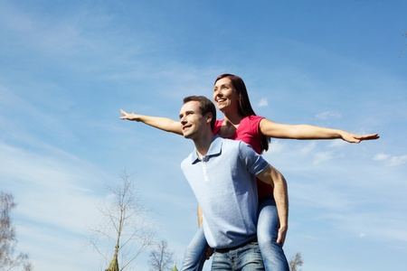 Happy man giving piggyback to his wife outdoors against blue sky photo
