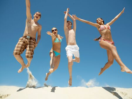 Portrait of four happy friends jumping energetically over sandy shore photo
