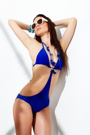 swimsuit: Portrait of a young girl posing in blue swimsuit and sunglasses