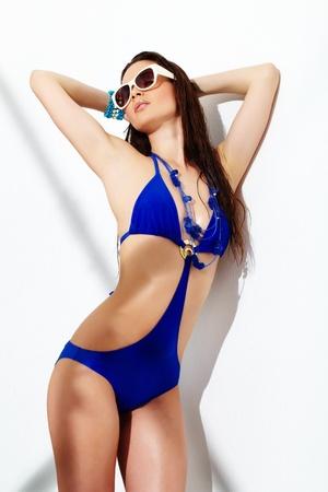 traje de bano: Retrato de una joven posando en gafas de sol y traje de ba�o azul  Foto de archivo