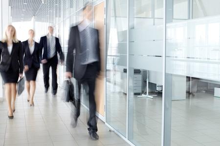 personas caminando: Varios empresarios caminando en el corredor
