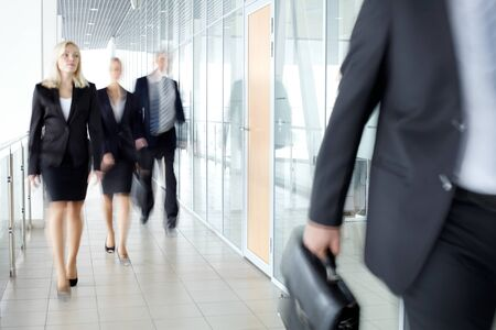corporation: Business people walking along the office corridor