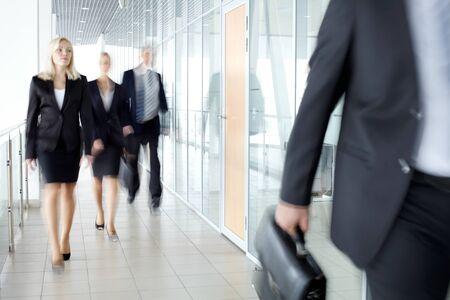 personas caminando: Empresarios caminando por el corredor de oficina