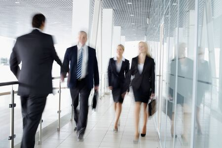 business people walking: Businesspeople moving along the corridor