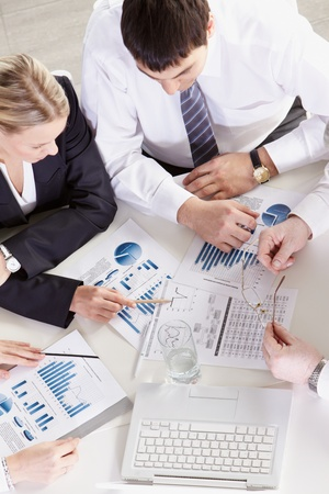 graphs: Above view of businesspeople discussing graphs