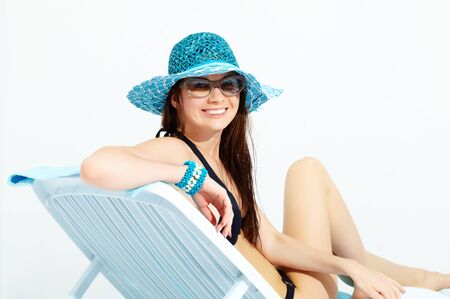 appealing attractive: Portrait of a young girl sitting in chaise lounge, looking at camera and smiling Stock Photo