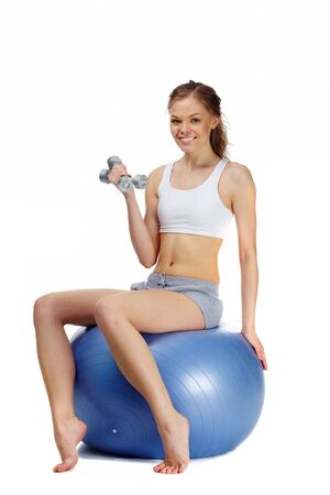 Portrait of a young girl sitting on gymnastic ball with dumbbells  photo