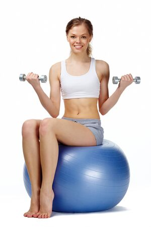 dumbbells: Portrait of a young girl sitting on gymnastic ball, looking at camera and smiling Stock Photo