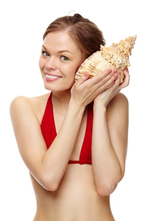 Portrait of a young girl in bikini holding a seashell  photo
