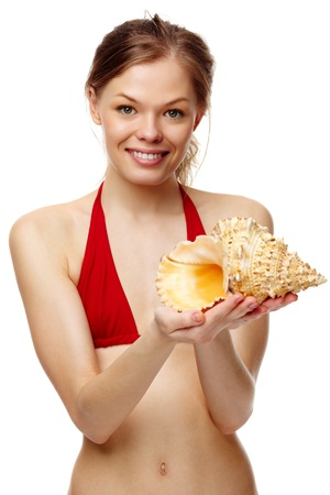 Portrait of a young girl in bikini with seashell looking at camera photo