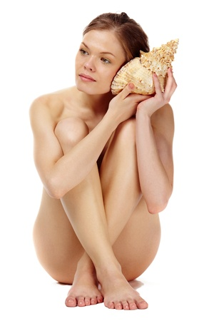 Portrait of a naked girl listening to the seashell  photo