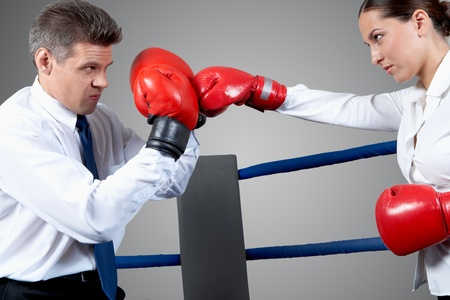 Portrait of aggressive businessman in boxing gloves fighting with serious female opposite him photo