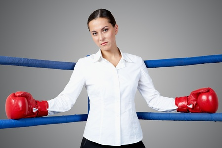 Portrait of strict businesswoman in boxing gloves looking at camera photo