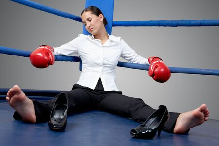 female soles: Portrait of tired businesswoman in boxing gloves sleeping on boxing ring