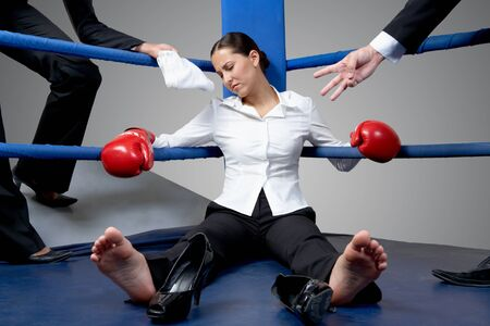Portrait of tired businesswoman in boxing gloves sleeping on boxing ring after hard game photo