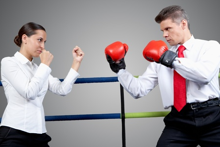 Portrait of aggressive businessman in boxing gloves and serious female in conflict with each other photo