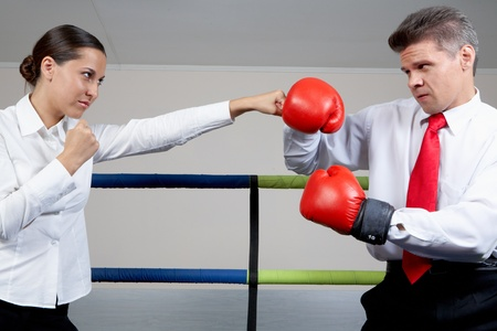 Portrait of aggressive businessman in boxing gloves fighting with serious female  photo