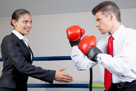 unfriendly: Portrait of aggressive businessman in boxing gloves fighting with positive female with her arm stretched for handshake Stock Photo