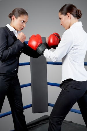 Photo of aggressive business women fighting with each other on boxing rink photo