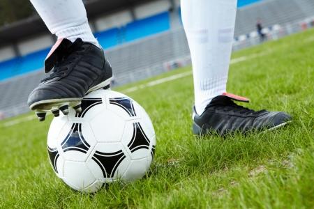 jugadores de futbol: Imagen horizontal de bal�n de f�tbol con el pie del jugador de tocarlo