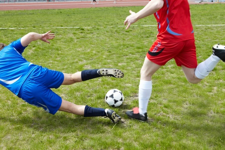Two footballers chasing ball on grass-field during game photo