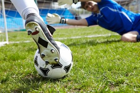 goal keeper: Horizontale beeld van voetbal bal met de voet van de speler schoppen het