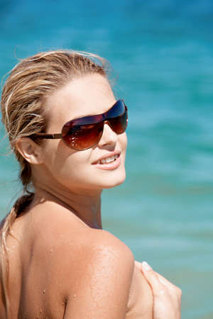 Portrait of beautiful female in sunglasses on background of blue ocean photo
