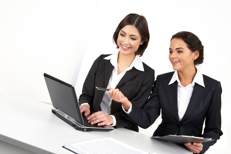 Two businesswomen working together with computer photo