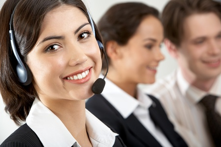 Close-up of a young businesswoman in headset looking at camera and smiling Stock Photo - 9727169