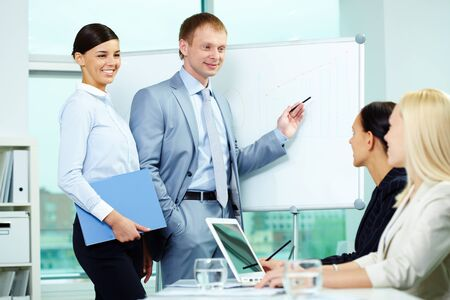 A business man explaining something on a whiteboard with pretty woman near by Stock Photo - 9821537