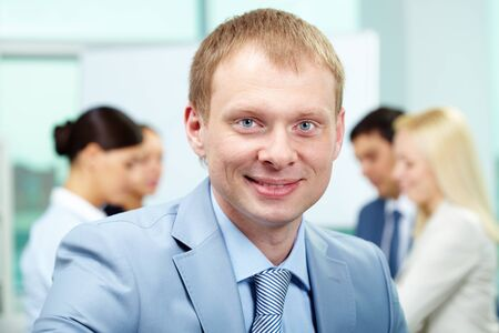 Portrait of smart employer looking at camera in working environment photo